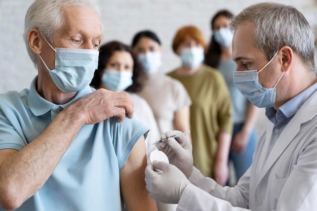 Hombre recibiendo vacuna inyectada por médico con máscara médica