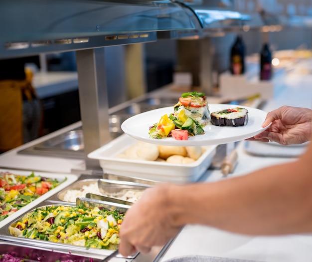 Hombre recoge comida en el buffet