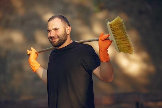 El hombre recoge hojas y limpia el parque.