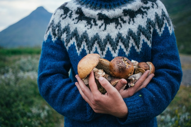Hombre recolector feliz y orgulloso en suéter de lana azul tradicional con adornos se encuentra en un camping en las montañas, sostiene en brazos una pila de hongos deliciosos y orgánicos