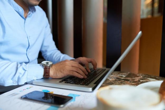 Hombre recortado ocupado escribiendo en el teclado del ordenador portátil desayunando
