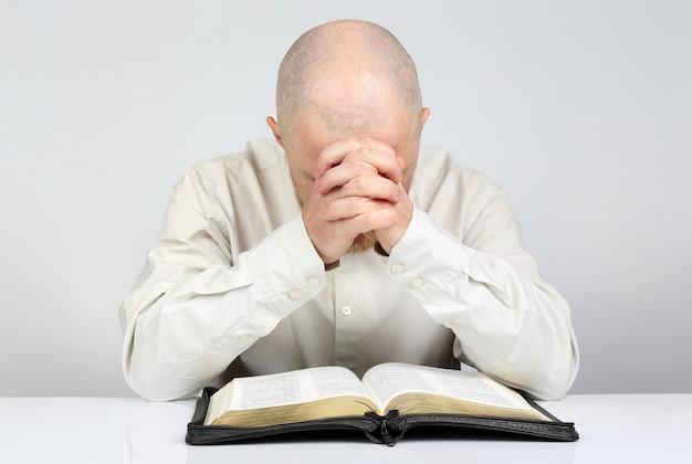 El hombre reflexiona sobre la lectura de un libro de la biblia
