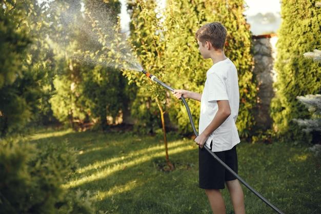 Hombre regando sus plantas en su jardín. hombre con camisa azul.