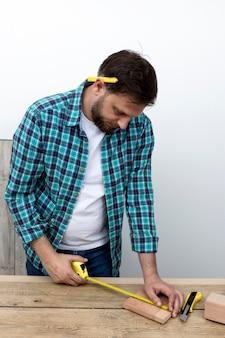 Hombre con regla y concepto de taller de carpintería de madera