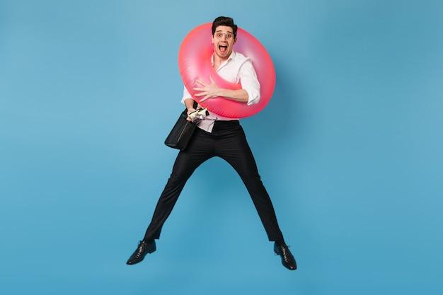 El hombre se regocija de vacaciones, saltando de la felicidad con un círculo inflable y una máscara de buceo en el espacio azul.