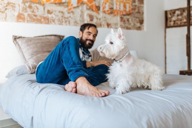 Hombre relajado en casa sentado en la cama con su perro