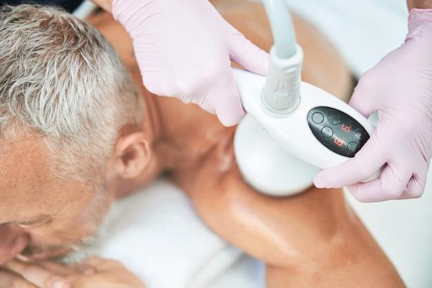 Un hombre relajado que se acuesta mientras se realiza un procedimiento de cavitación por ultrasonido no invasivo en su hombro