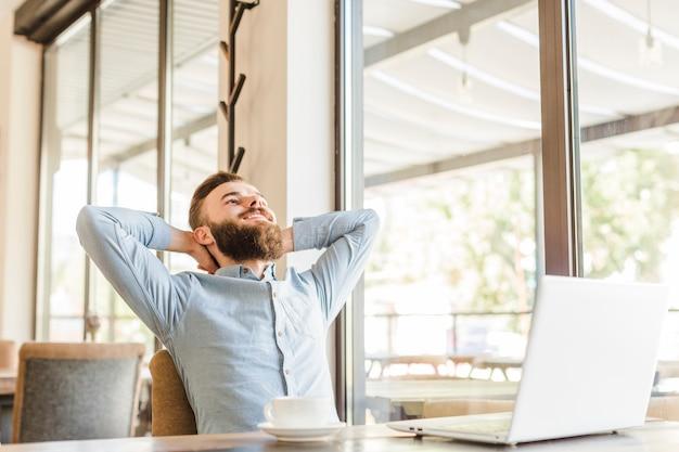 Hombre relajado que se sienta en el café con la taza de café y el ordenador portátil en el escritorio