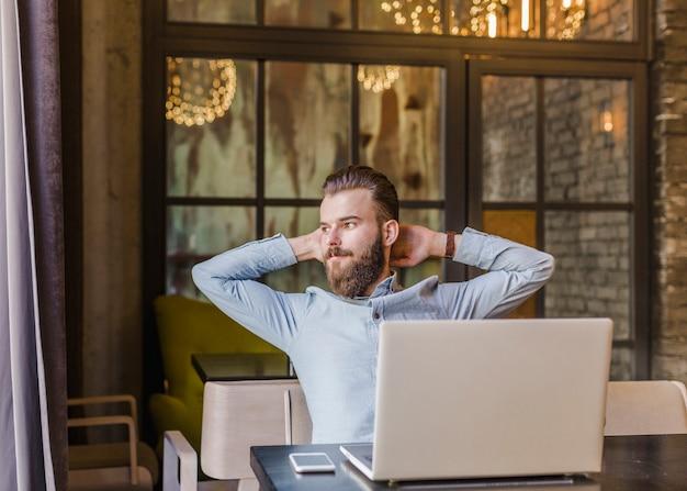 Hombre relajado que se sienta en restaurante con el ordenador portátil y el teléfono móvil en el escritorio