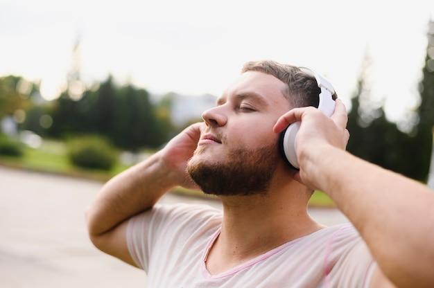 Hombre relajado que sostiene los auriculares con las manos