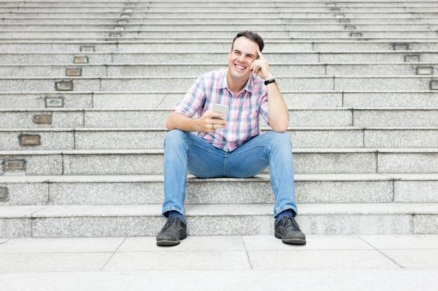 Hombre relajado que usa smartphone en la escalera de la ciudad