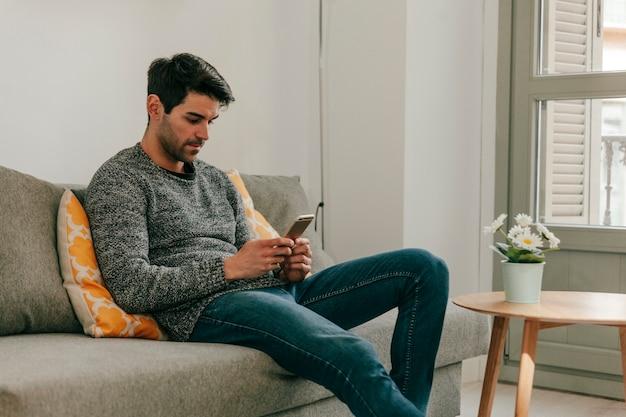 Hombre relajado con smartphone en el sofá