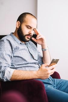 Hombre relajado con teléfono inteligente en silla