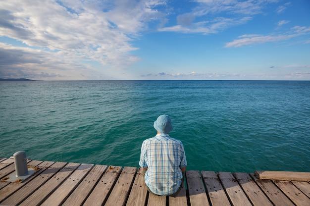 Hombre relajante en el muelle del mar