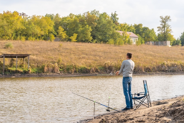 Hombre relajante y pescando junto al lago