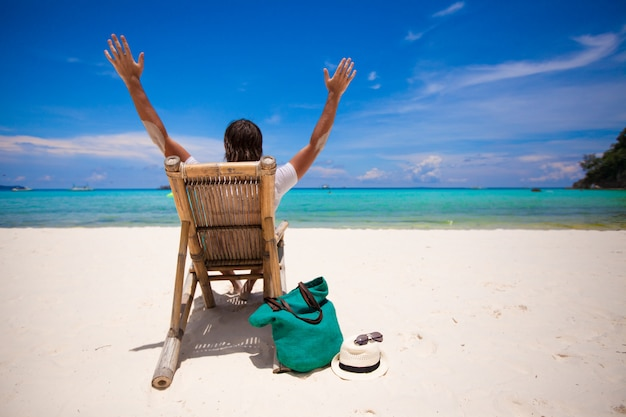 Hombre relajante en la silla de madera en la playa de arena