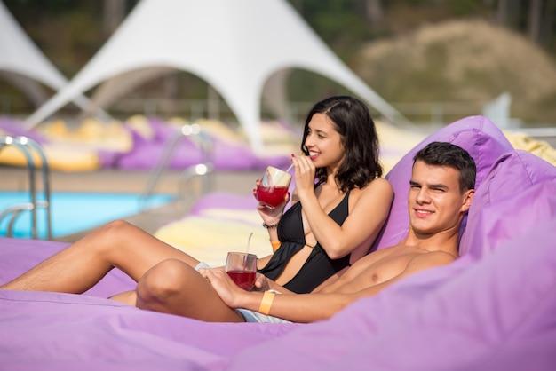 Hombre relajante con su novia junto a la piscina