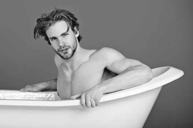 Hombre relajarse en el baño, chico con cuerpo musculoso y pecho desnudo tiene cabello de moda sentado en bañera blanca, spa y belleza, salud.