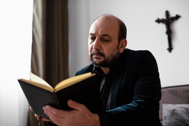 Hombre religioso leyendo un libro sagrado en casa