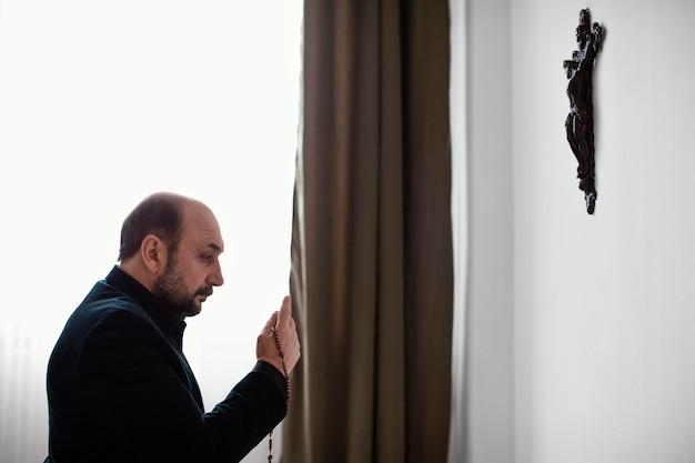 Hombre religioso rezando en casa
