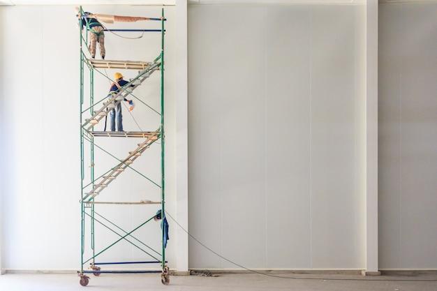 Hombre relleno de silicona para sellar en el trabajo en altura en el sitio de construcción