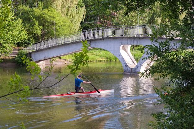 El hombre está remando en un bote de kayak en el lago de la ciudad en un día soleado
