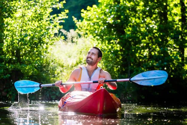 Hombre remando con kayak en el río para deportes acuáticos