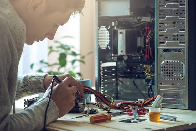 El hombre reparador está tratando de arreglarlo usando las herramientas en la computadora que está en un lugar de trabajo en la oficina