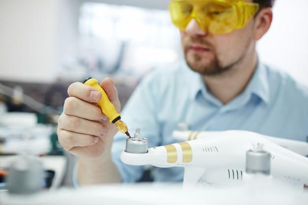 Hombre reparando drones en taller moderno