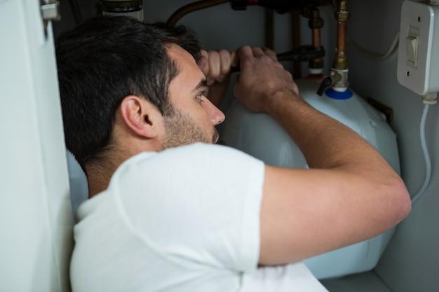 Hombre reparando un fregadero de cocina