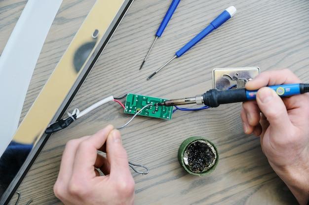 El hombre está reparando la fuente de alimentación de la lámpara. él sostiene una placa electrónica y un soldador. vista superior.