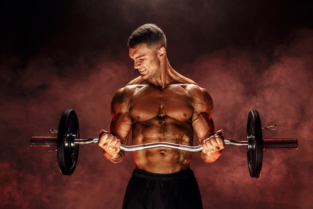 Hombre resistente haciendo ejercicio con barra pesada