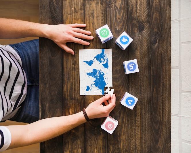 Hombre resolviendo rompecabezas de mapa mundial cerca de bloques de iconos de redes sociales