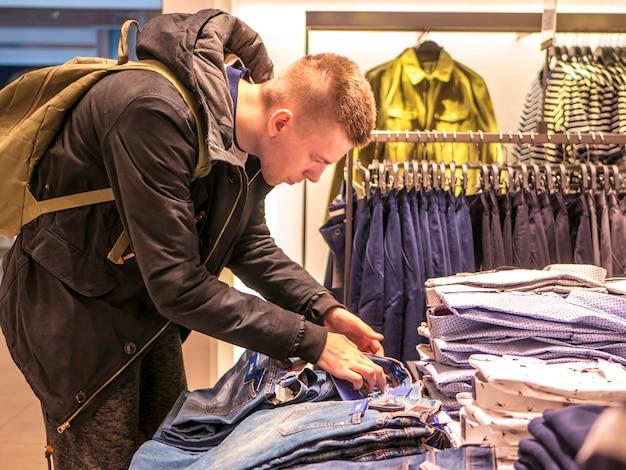 Hombre en el retrato de la tienda de ropa que elige y que recoge la ropa