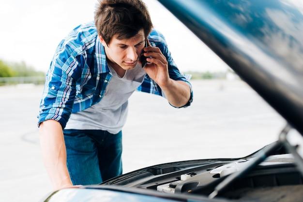 Hombre revisando el motor y hablando por teléfono