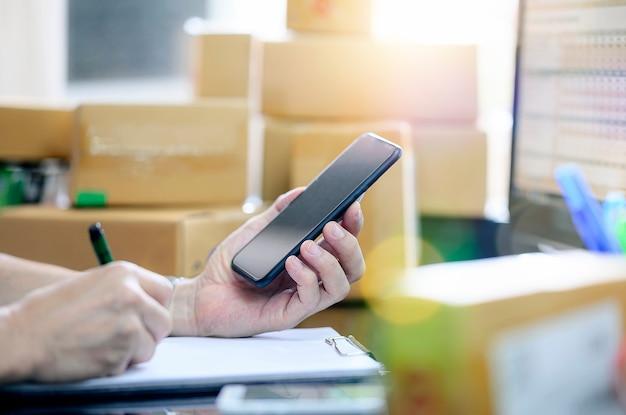 Hombre revisando la orden de compra en el teléfono móvil y escriba la entrega en el papeleo