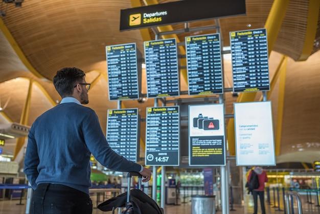 Hombre revisando su vuelo en la pantalla del horario en el aeropuerto