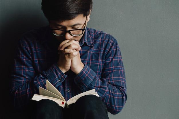 Hombre rezando en la sagrada biblia en la mañana. mano de muchacho adolescente con biblia rezando,