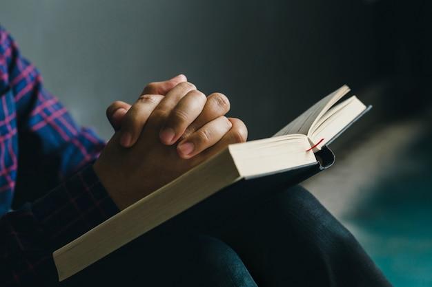 Hombre rezando en la sagrada biblia en la mañana. mano de niño adolescente con oración bíblica, cristianos y concepto de estudio bíblico espacio de copia.
