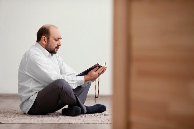 Hombre rezando en el suelo en el interior