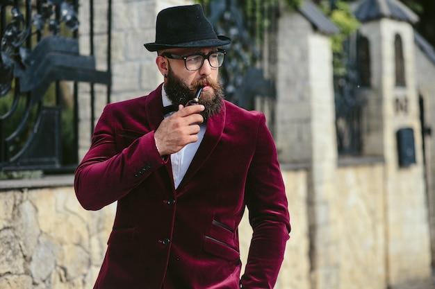 Un hombre rico con barba fuma cigarrillo electrónico.