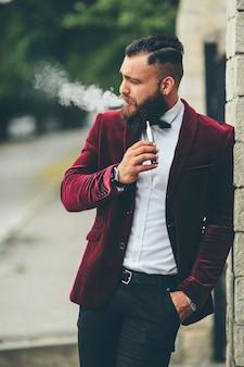 Hombre rico con barba fuma cigarrillo electrónico