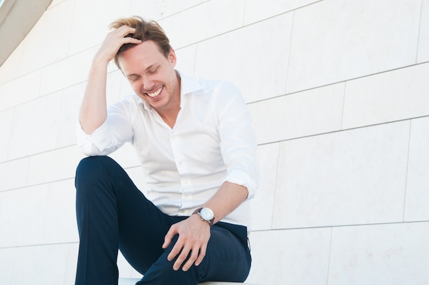 Hombre riendo despeinando su cabello