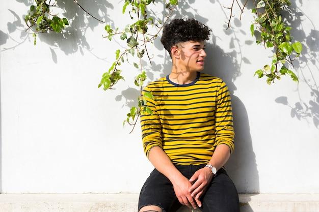 Hombre rizado en camisa a rayas sentado y mirando a otro lado