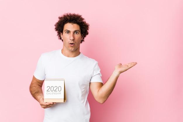 El hombre rizado caucásico joven que sostiene un calendario 2020 impresionó sostener el espacio de la copia en la palma.