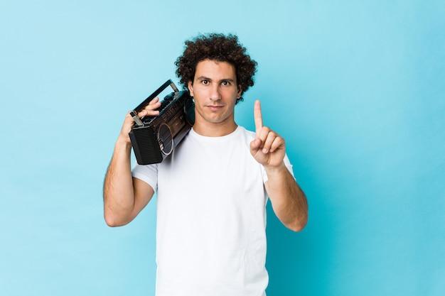 Hombre rizado caucásico joven sosteniendo un guetto blaster mostrando el número uno con el dedo.