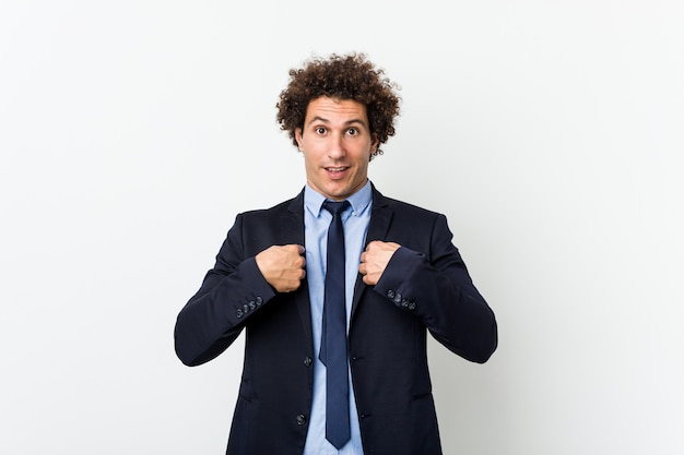 El hombre rizado del negocio joven contra el fondo blanco sorprendió señalar con el dedo, sonriendo ampliamente.