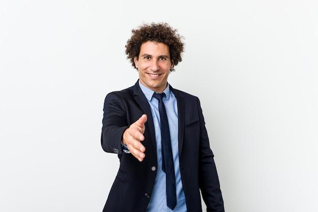 Hombre rizado del negocio joven contra la pared blanca que estira la mano en la cámara en gesto del saludo.