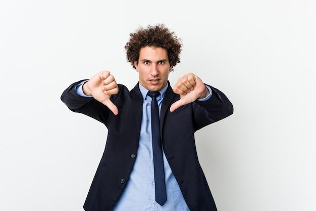 Hombre rizado del negocio joven contra la pared blanca que muestra el pulgar hacia abajo y que expresa aversión.
