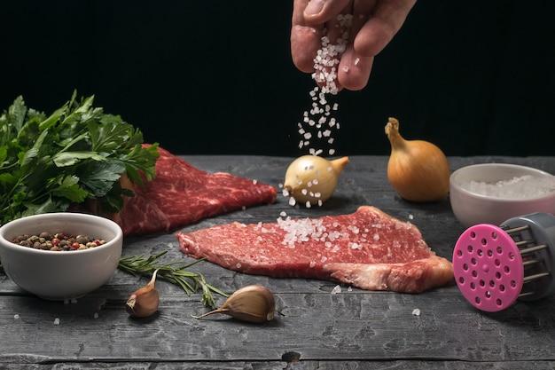 El hombre rocía abundantemente un trozo de carne con sal marina gruesa. cocinar platos de carne.